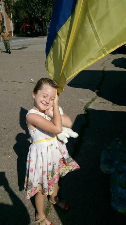 Мережу підкорило фото дівчинки, яка після трьох років життя в окупації горнеться до прапора вільної України