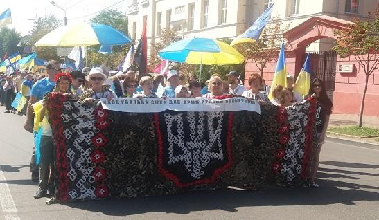 На Марші захисників України в Києві волонтери з Черкас розгорнули… маскувальну сітку з виплетеним бойовим Тризубом